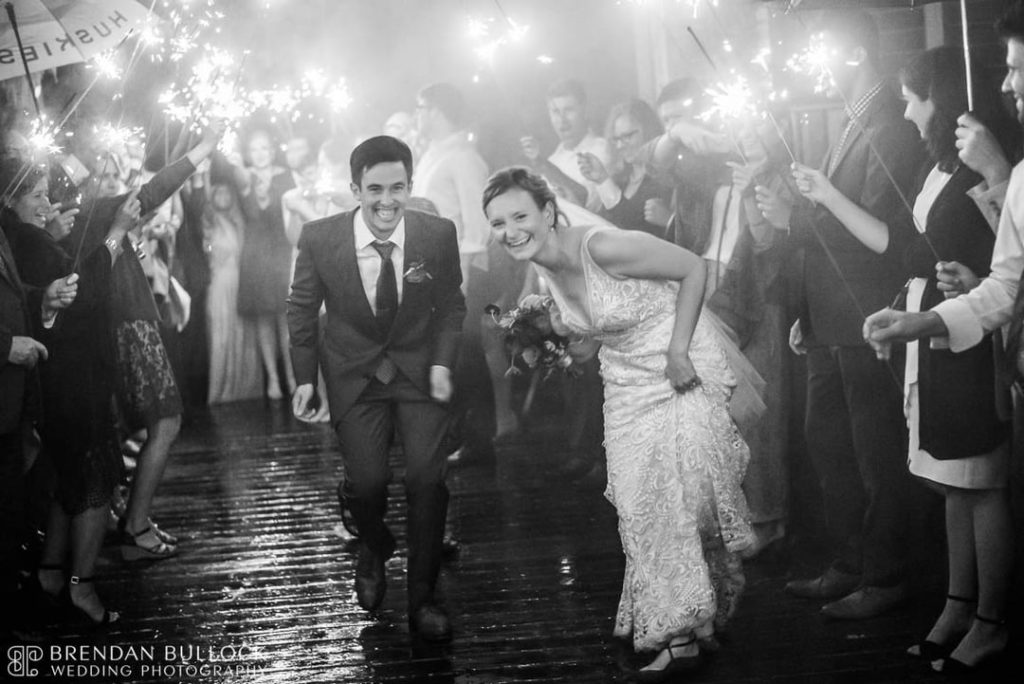 Bride and Groom Walking Between Their Wedding Guests